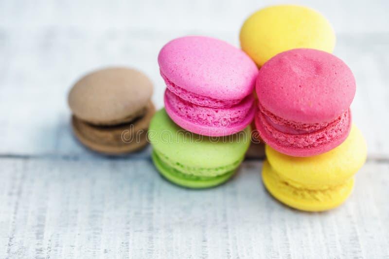 在白色木桌上的充满活力的五颜六色的macarons 免版税图库摄影