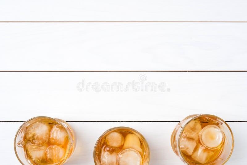 在白色木桌上的威士忌酒玻璃 库存照片