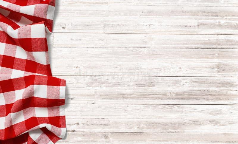 在白色木桌上的红色方格的野餐桌布 免版税图库摄影