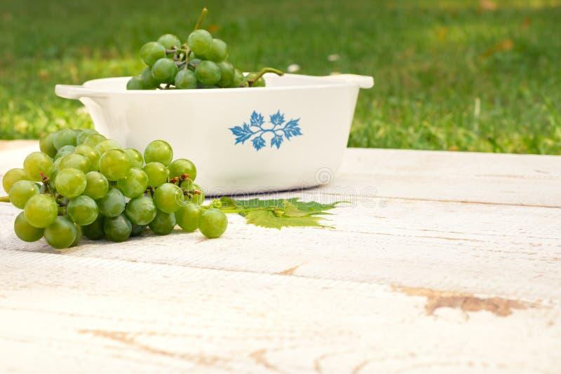 在白色木桌上的葡萄 库存照片