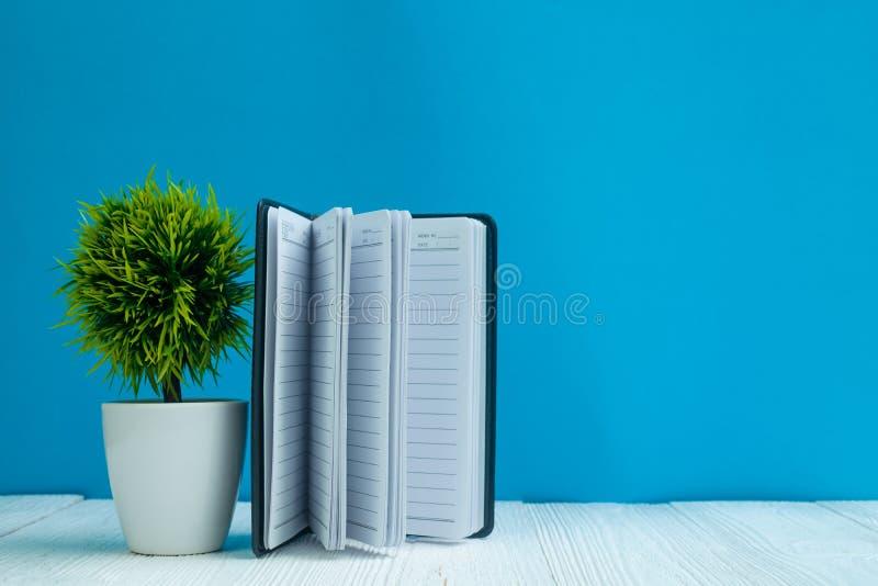 在白色木桌前面蓝色墙壁背景wi的空白的笔记本 免版税库存图片