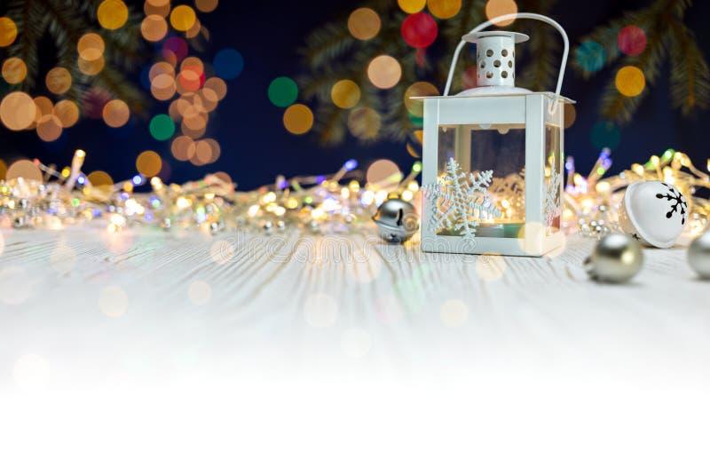 在白色木的灼烧的蜡烛灯笼和圣诞节装饰 免版税库存照片