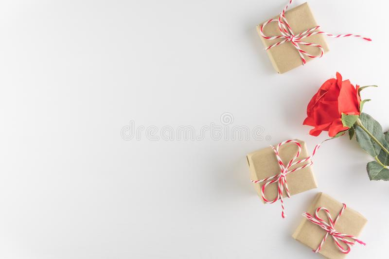 在白色木纹理背景和红色玫瑰色花隔绝的礼物盒,情人节快乐 背景上色节假日红色黄色 免版税库存图片