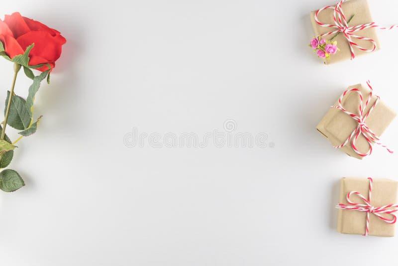 在白色木纹理背景和红色玫瑰色花隔绝的礼物盒,情人节快乐 背景上色节假日红色黄色 库存图片