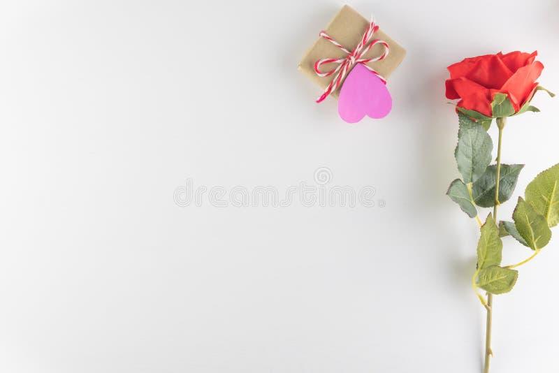 在白色木纹理背景和红色玫瑰色花隔绝的礼物盒,情人节快乐 背景上色节假日红色黄色 库存照片