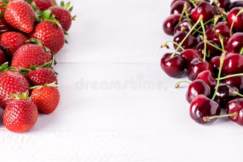 在白色木背景甜草莓和樱桃框架拷贝空间的新鲜的美丽的成熟莓果 库存图片