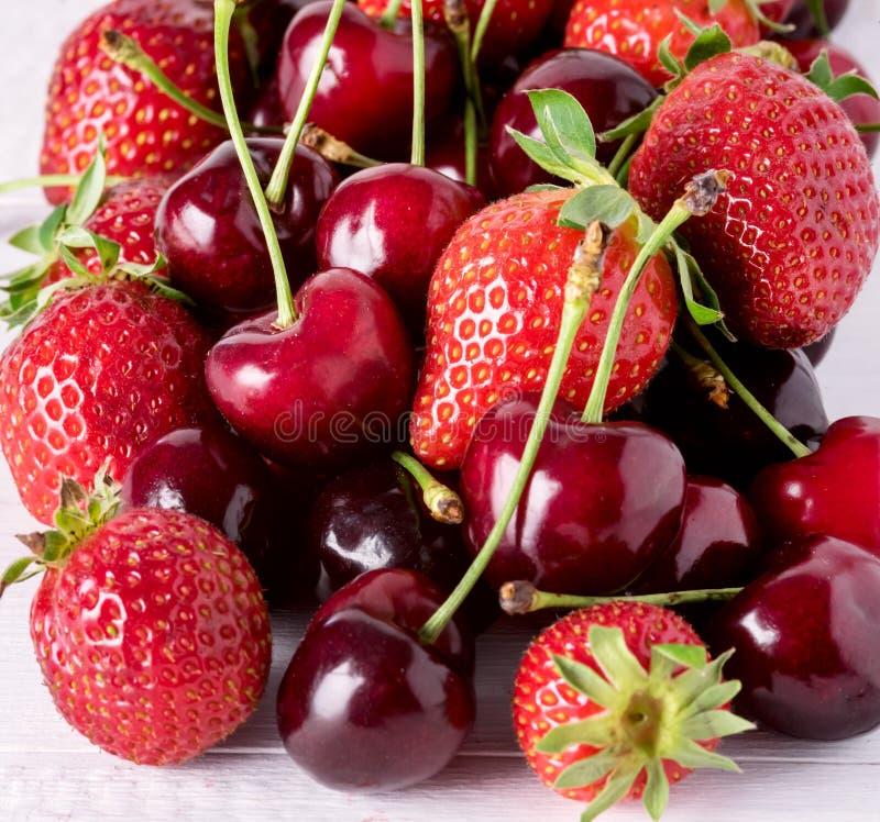 在白色木背景甜草莓和樱桃正方形关闭的新鲜的美丽的成熟莓果 库存图片