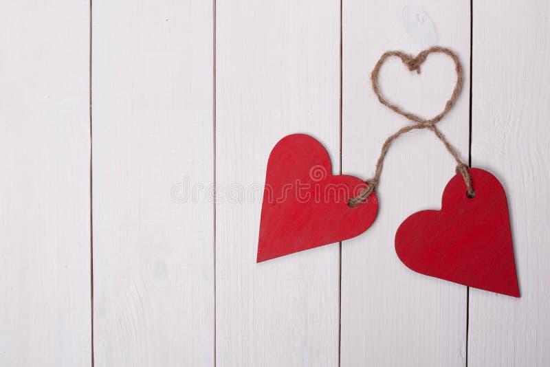 在白色木背景的两红色心脏 事为愉快的圣情人节 免版税库存图片