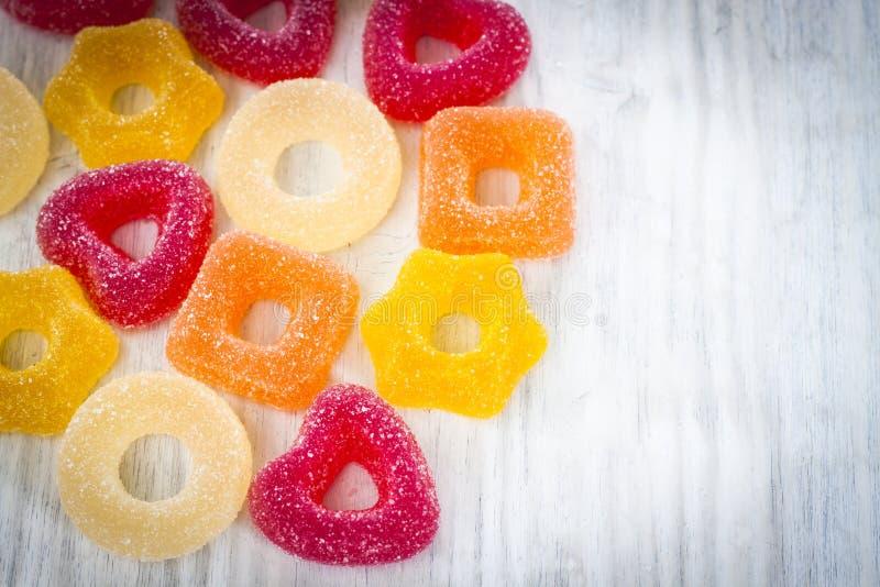 在白色木背景的五颜六色的果冻糖果 免版税库存图片