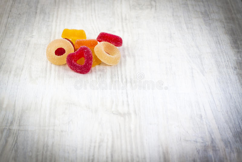 在白色木背景的五颜六色的果冻糖果 库存图片