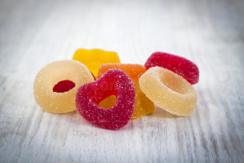 在白色木背景的五颜六色的果冻糖果 图库摄影