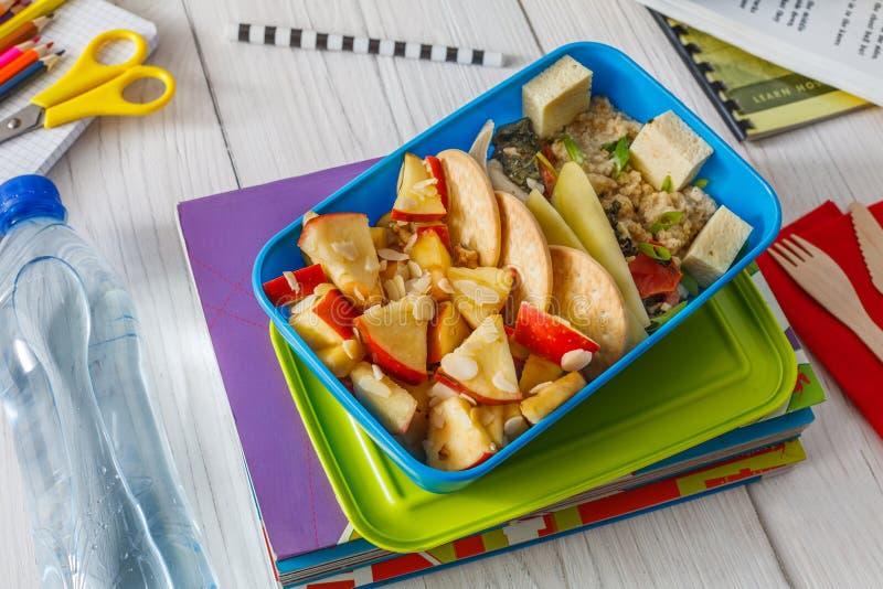 在白色木背景的健康学校午餐箱子 库存图片