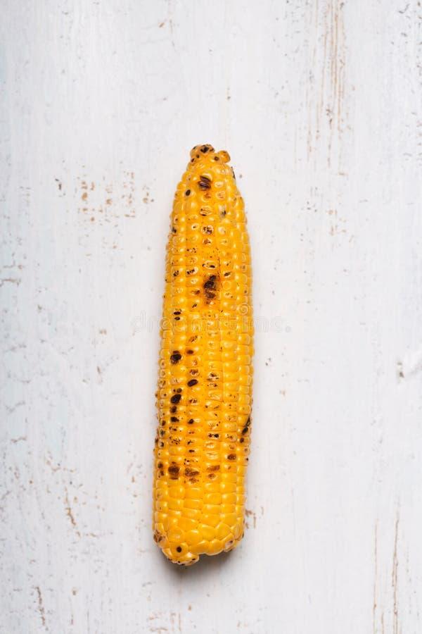 在白色木背景的唯一烤玉米棒子 库存照片