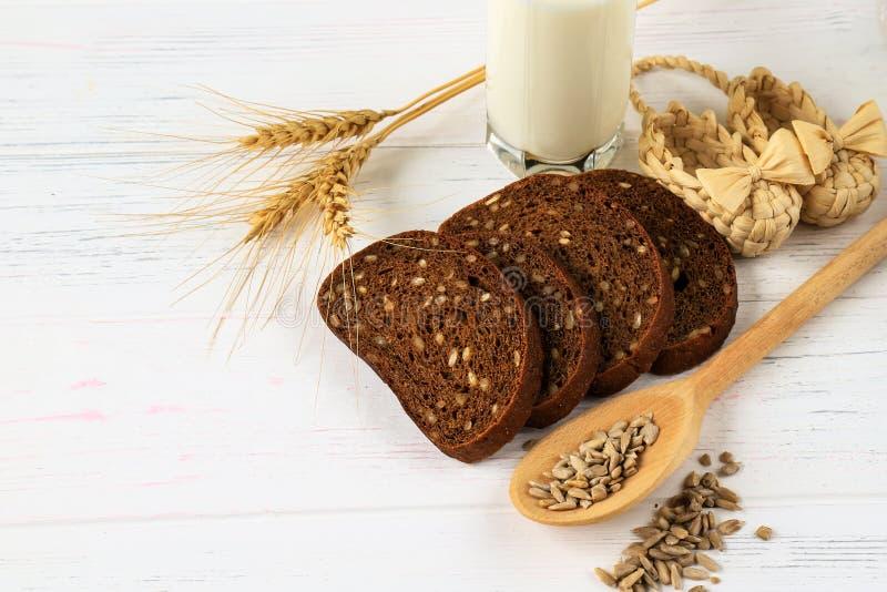 在白色木背景的土气早餐-面包、向日葵、麦子的种子在一把轻的匙子,耳朵和一杯牛奶 库存图片