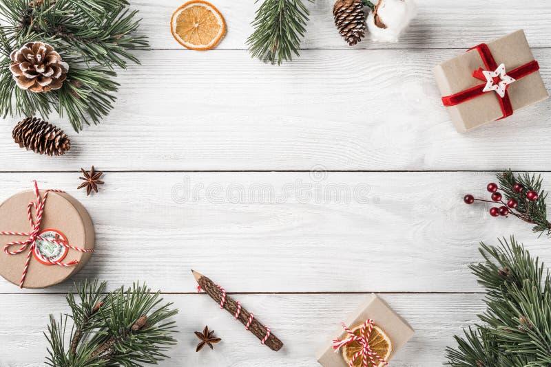 在白色木背景的圣诞礼物箱子与冷杉分支,杉木锥体 图库摄影