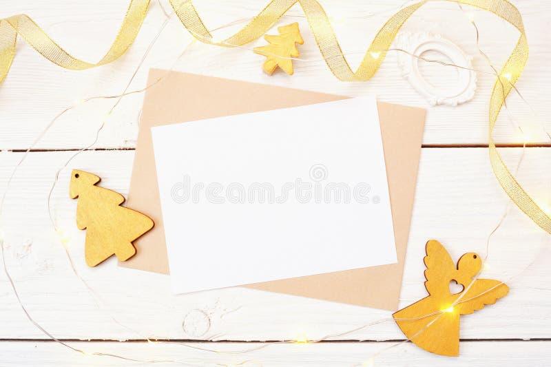 在白色木背景的圣诞节邮件与一棵金黄天使和圣诞树 平的位置顶视图照片大模型 免版税库存图片