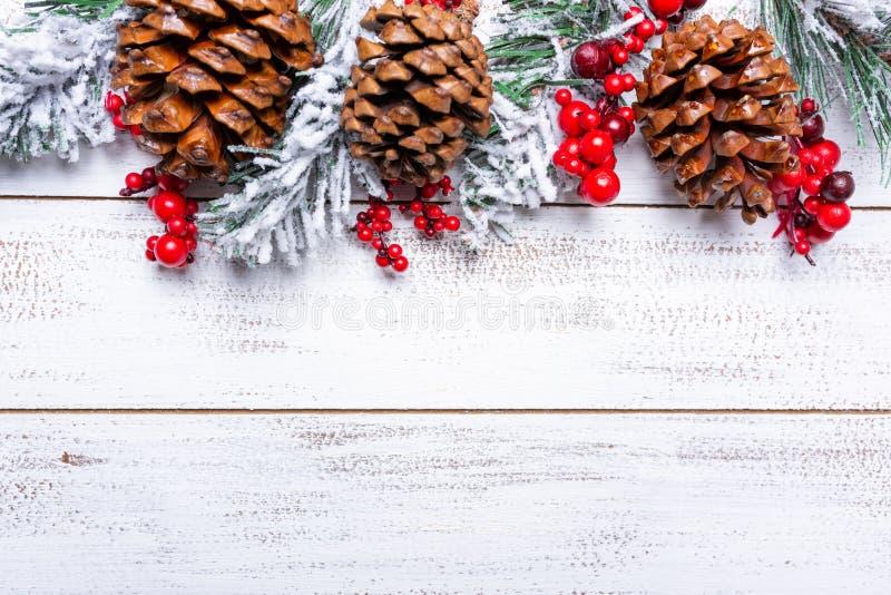 在白色木背景的圣诞装饰与拷贝空间 杉木锥体、诗歌选、莓果和杉木分支 免版税图库摄影