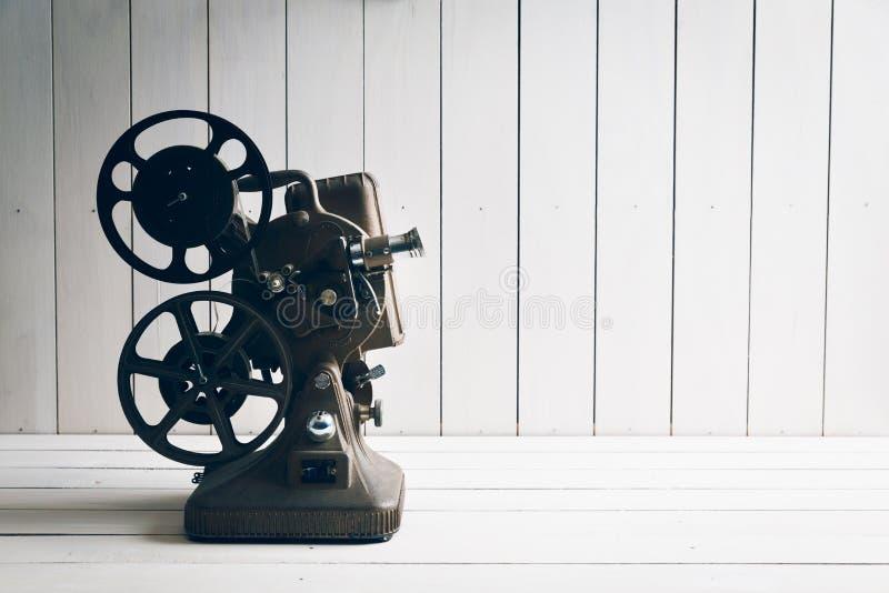 在白色木背景的放映机 免版税库存照片