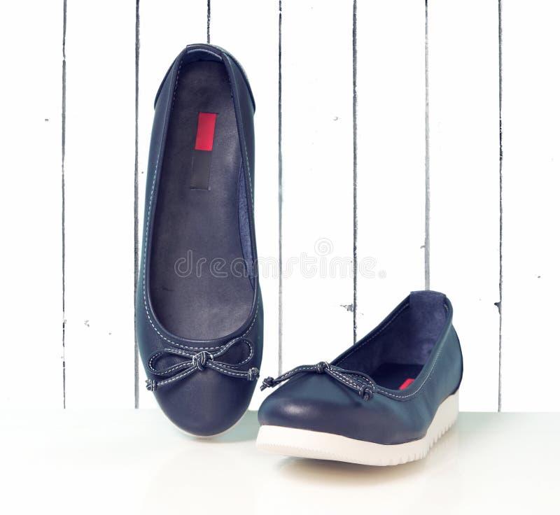 在白色木背景的皮革平的简单的女性鞋子 免版税库存照片