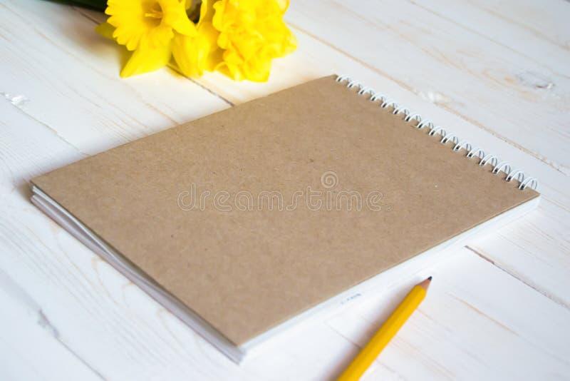 在白色木背景的空白的笔记薄与铅笔和花 免版税库存照片