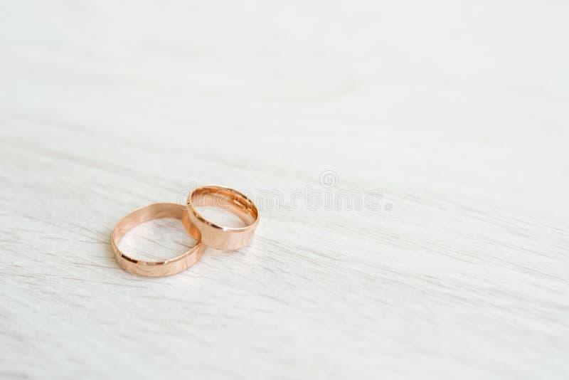 在白色木背景的结婚戒指与拷贝空间 爱和婚姻的概念 库存图片