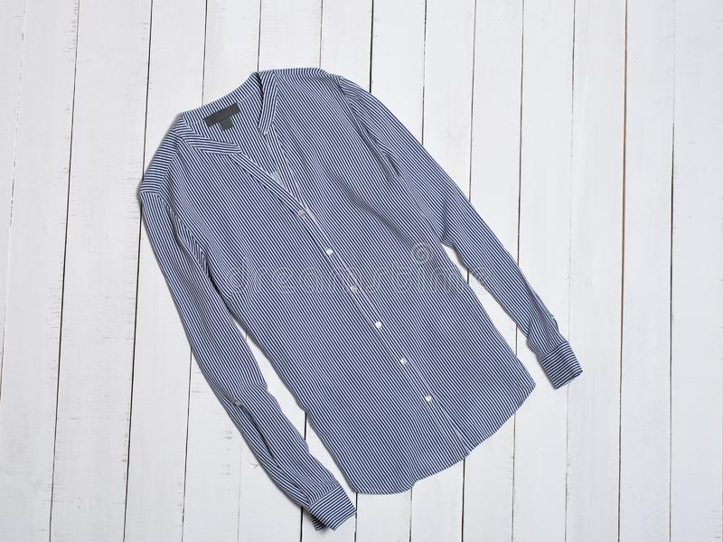 在白色木背景的蓝色镶边棉布衬衣 秀丽蓝色聪慧的概念表面方式构成妇女 库存图片