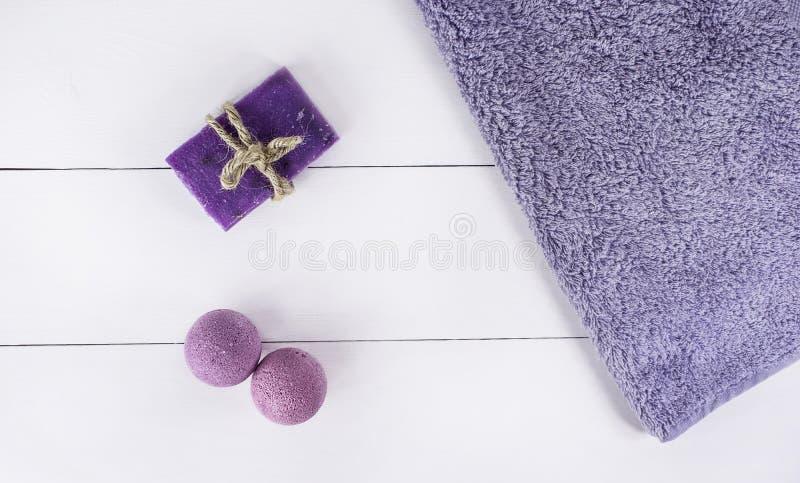 在白色木背景,卫生学的顶视图产品的平的被放置的温泉浴 炸弹和肥皂从淡紫色与毛巾 库存照片