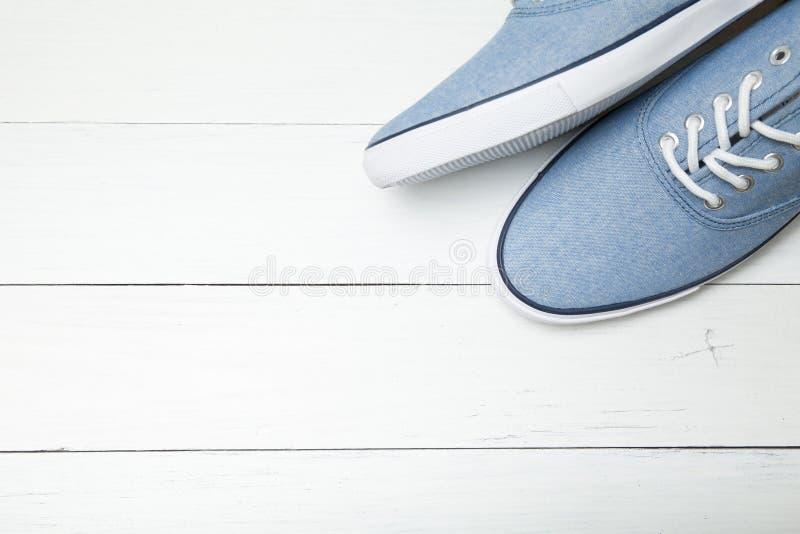 在白色木背景,文本的空的空间的软的舒适的蓝色运动鞋 免版税库存照片