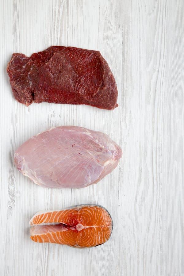 在白色木背景,顶视图的未煮过的未加工的牛肉肉,火鸡胸脯和鲑鱼排 平的位置 库存图片