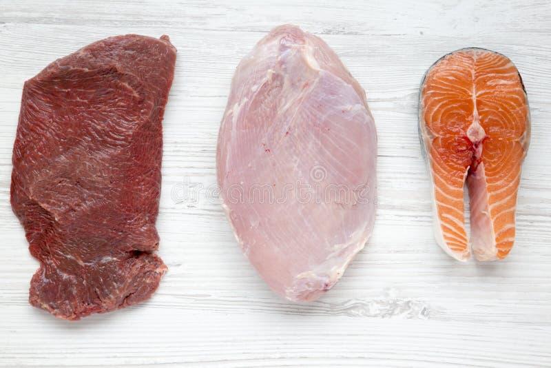在白色木背景,顶视图的未煮过的未加工的牛肉肉,火鸡胸脯和鲑鱼排 平的位置 免版税库存照片