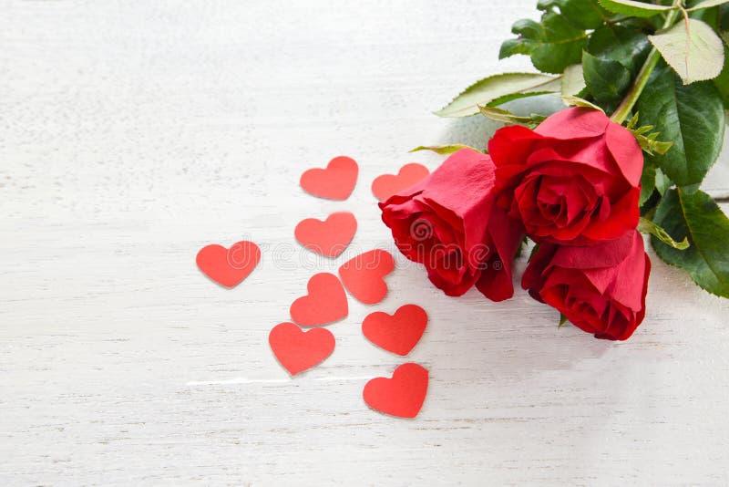在白色木背景/浪漫爱小红心的情人节红色玫瑰色花 库存照片