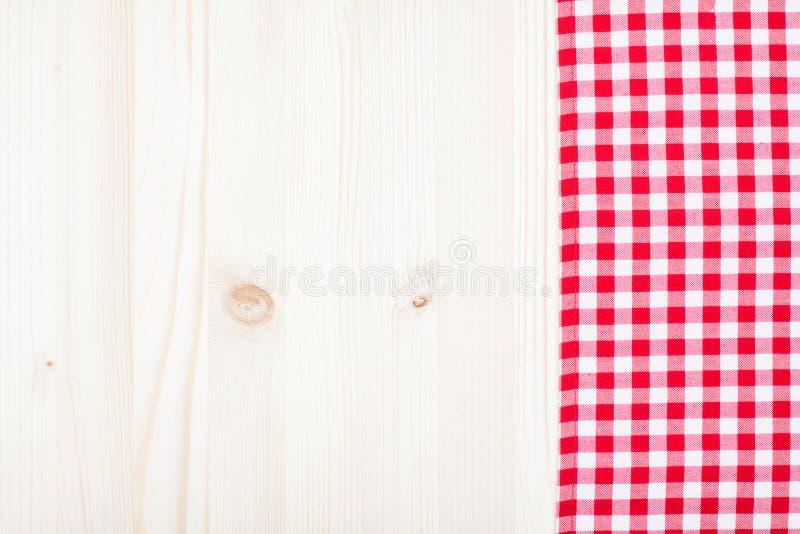 在白色木头的红色格子花呢披肩布料 免版税库存图片