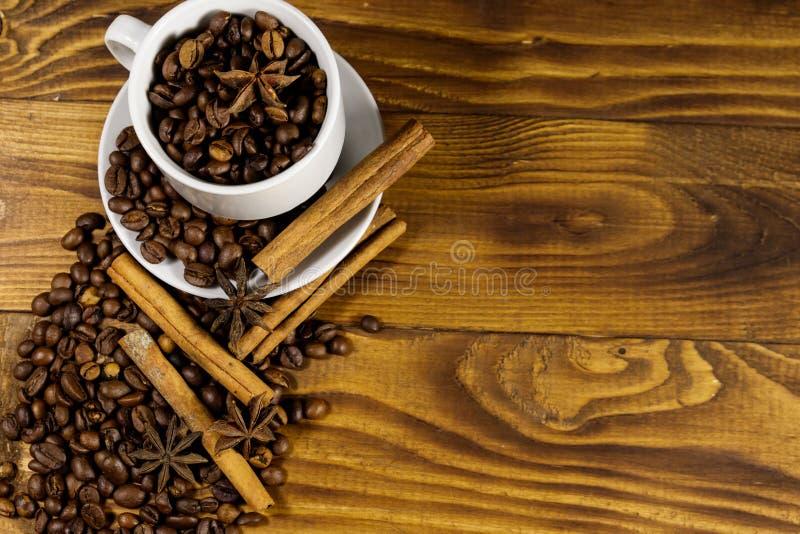 在白色杯子、八角和肉桂条的咖啡豆在木桌上 r 免版税库存图片