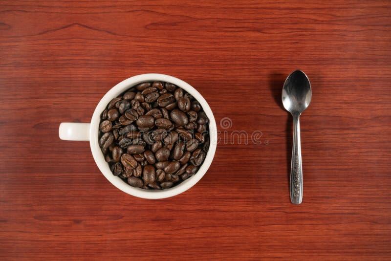 在白色杯子和匙子的咖啡豆有木背景 免版税库存图片