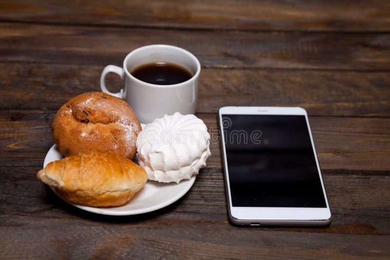 在白色杯子和手机的咖啡用新月形面包,蛋糕,蛋白软糖 库存照片
