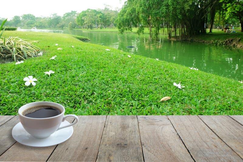 在白色杯子在木前景和花的咖啡在地板上有庭院或公园背景 库存照片