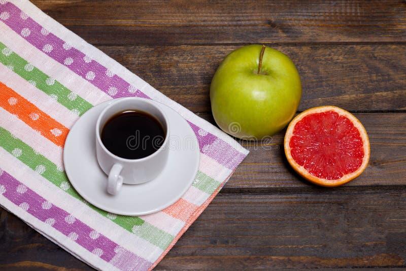 在白色杯子的咖啡用绿色苹果和切的葡萄柚 库存照片