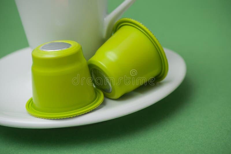 在白色杯子的塑料浓咖啡咖啡胶囊在白色背景的coffe 免版税库存照片