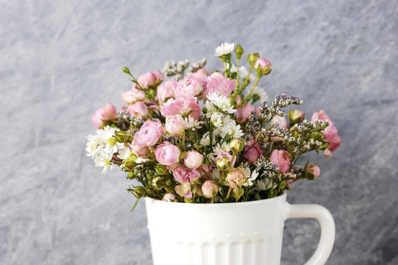 在白色杯子的微型桃红色玫瑰花 库存照片