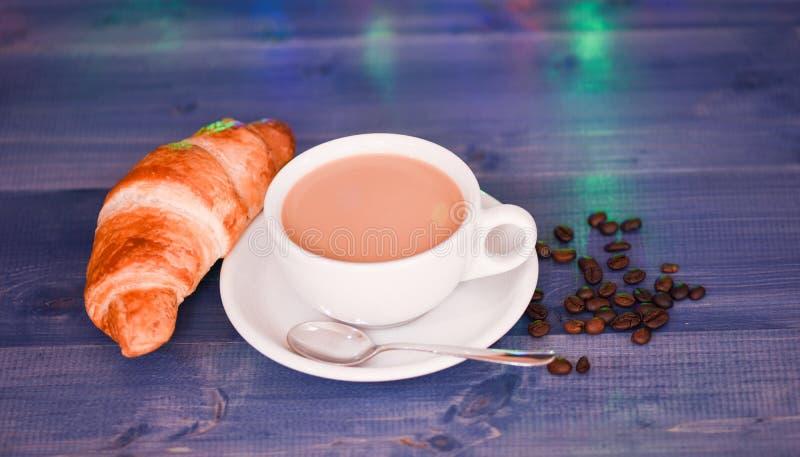 在白色杯子的新鲜的煮的咖啡或杯子新月形面包和豆在木蓝色背景 咖啡饮料新的寒假 图库摄影