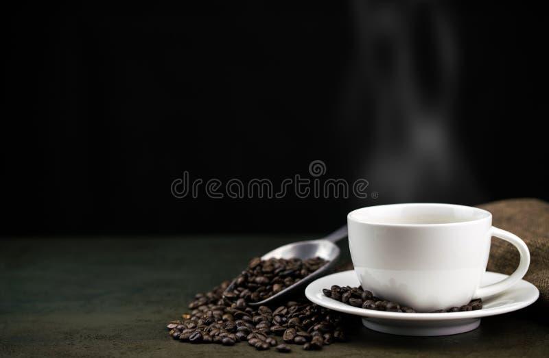 在白色杯子的热的咖啡有烘烤咖啡豆、袋子和瓢的在石桌上在黑背景中 免版税库存照片