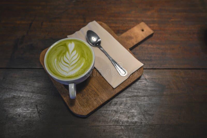 在白色杯子的热的Matcha在木桌上的拿铁有小匙子的和餐巾 免版税库存照片