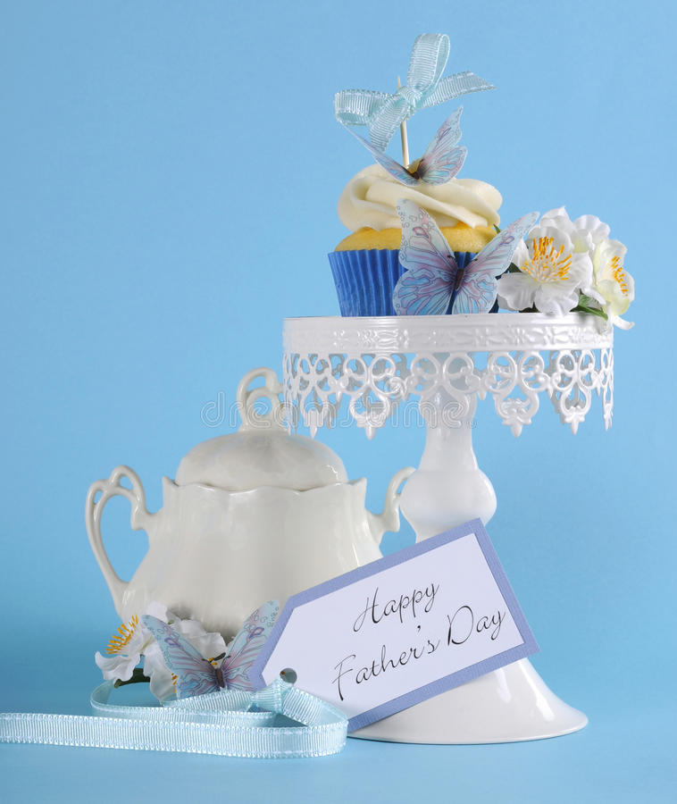 在白色杯形蛋糕立场的愉快的父亲节蓝色蝴蝶题材杯形蛋糕 免版税库存图片