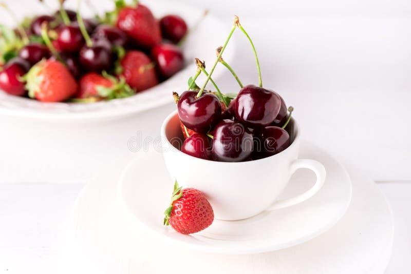 在白色杯成熟水多的樱桃关闭的新鲜和美丽的樱桃白色背景 图库摄影