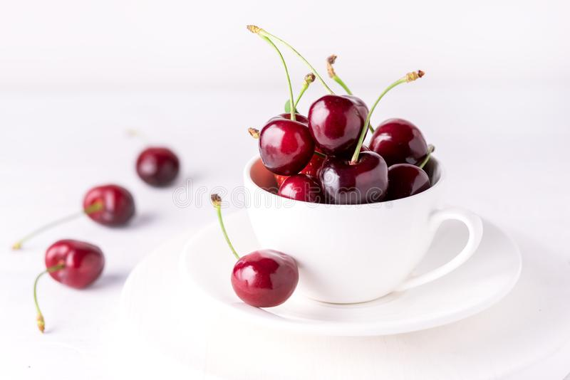 在白色杯成熟水多的樱桃关闭的新鲜和美丽的樱桃白色背景 免版税库存照片