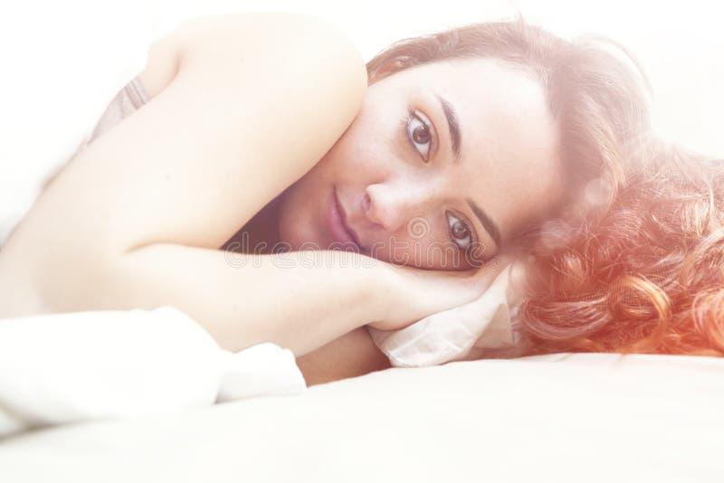 在白色板料之间的床上的年轻美丽的女孩 免版税库存图片