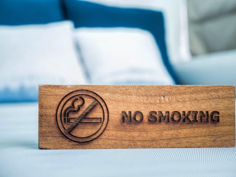 在白色板料床上的禁烟标志在旅馆客房 免版税库存照片