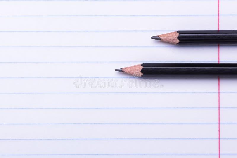 在白色板料的两支黑石墨铅笔在线回到学校的拷贝空间,教育概念 库存照片