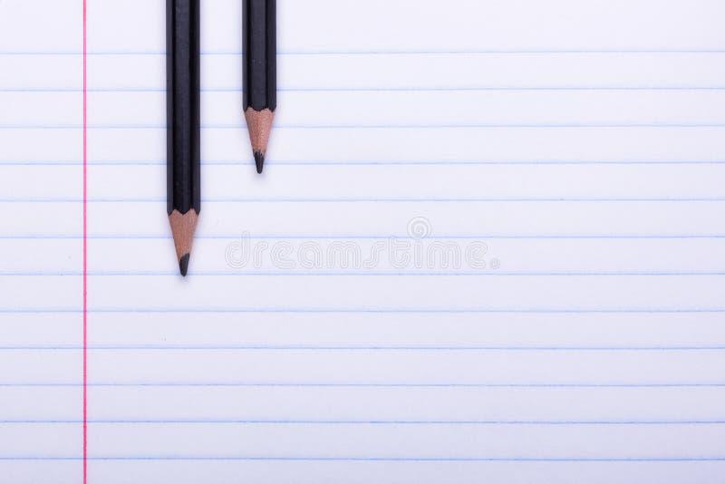 在白色板料的两支黑石墨铅笔在线回到学校的拷贝空间,教育概念 免版税库存照片