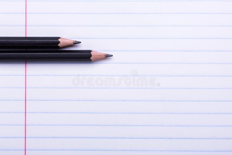 在白色板料的两支黑石墨铅笔在线回到学校的拷贝空间,教育概念 免版税图库摄影
